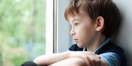 Sad child looking out a window