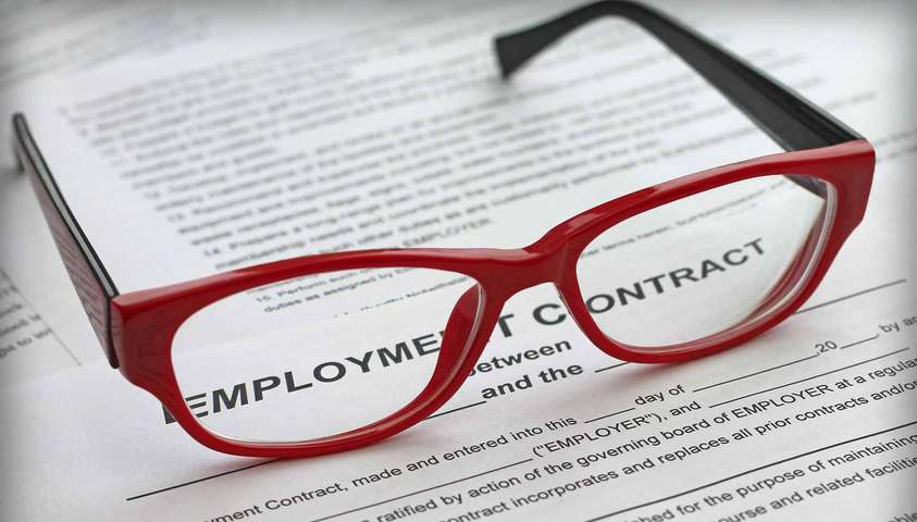 Pair of glasses on top of an employment contract