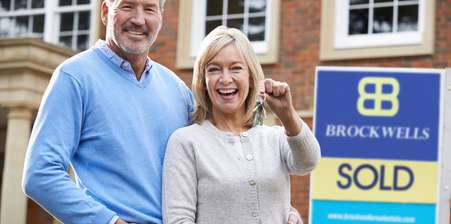 Elderly couple celebrating buying their new house