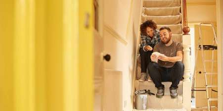 Young couple sat on the stairs whilst decorating a house