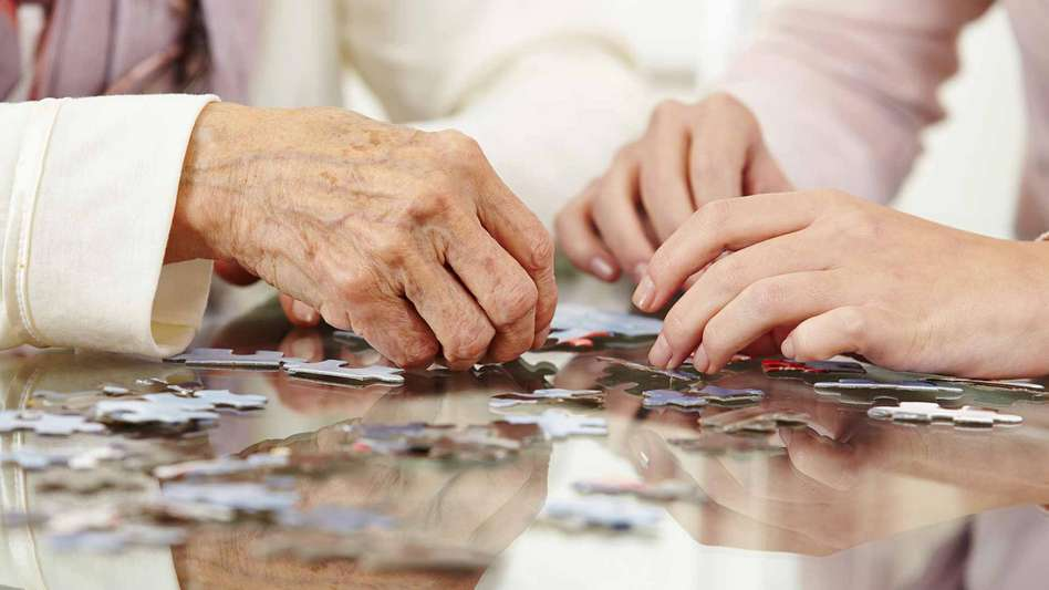 An elderly and young woman playing with a jigsaw