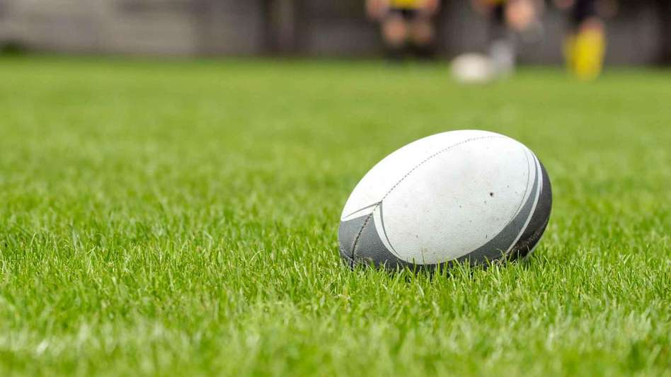 Rugby ball lying upon a rugby pitch