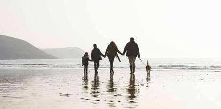 Family walking along a beach at sunset