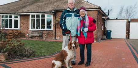 Elderly English couple outside their house with their dog